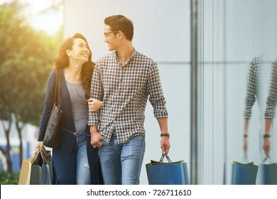 Young happy couple walking outdoors after shopping