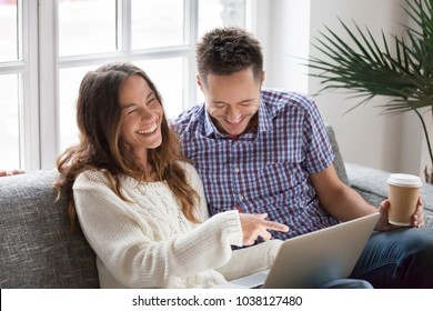Young happy couple watching funny video online, cheerful family having fun with laptop sitting on sofa at home, boyfriend and girlfriend friends laughing out loud at internet hilarious joke together