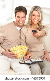 Young happy couple watching TV at home