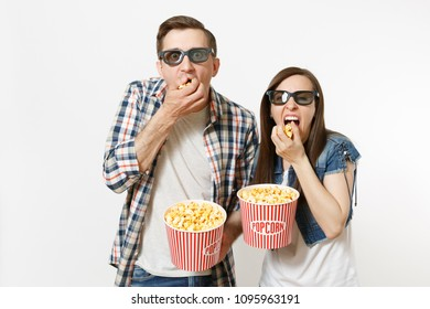 Young happy couple, woman and man in 3d glasses and casual clothes watching movie film on date, holding buckets of popcorn, eating isolated on white background. Emotions in cinema concept
