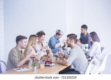 Young happy coworkers talking and eating lunch together