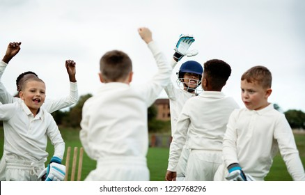 Young happy cricketers cheering on the field