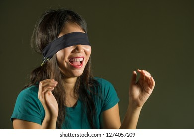 young happy and cute blindfolded Asian Korean teenager girl excited playing dangerous internet viral challenge isolated on dark background under edgy and dramatic studio light