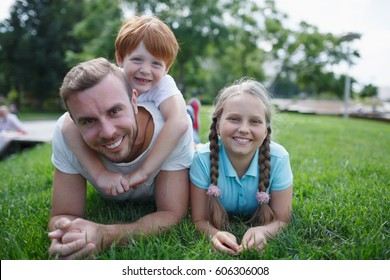 Young happy dad with cute little kids lying on green grass in summer park. Father with son and daughter playing together outdoors