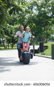 Young happy dad with cute little daughter riding scooter together in summer park outdoors and posing to camera