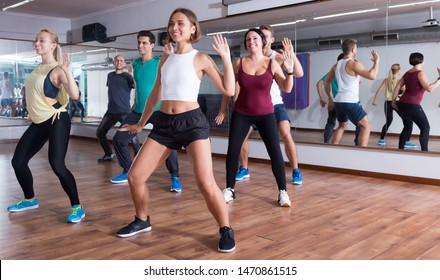 Young happy dansers studying zumba elements in dancing class