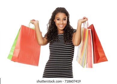 Young and happy dark skinned woman with shopping bags on white background