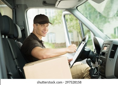 Young Happy Delivery Man With Cardboard Box Checking List In Van