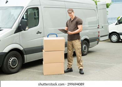 Young Happy Delivery Man With Cardboard Boxes Writing On Clipboard