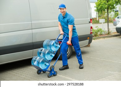 Young Happy Delivery Man Holding Trolley With Water Bottles