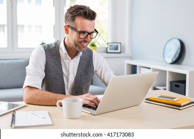 Young happy designer working on laptop from home - freelance concept