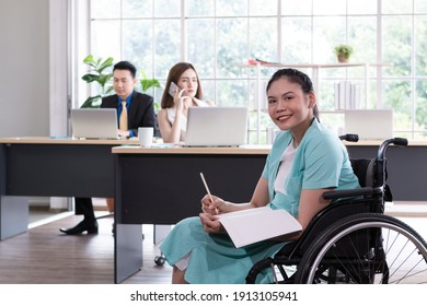 Young happy disabled Businesswoman on Wheelchair in modern office. Confident disabled businesswoman in creative office. Young woman in wheelchair working in office.