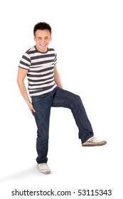 Young happy easygoing casual man standing on one leg isolated on white background