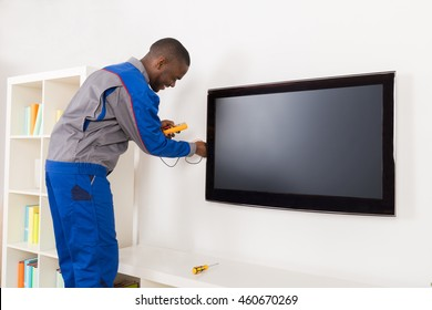 Young Happy Electrician Checking Television With Multimeter