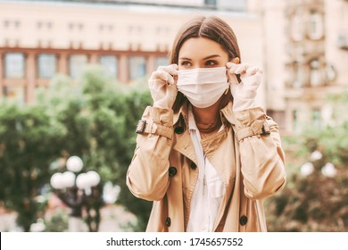 Young happy elegant girl in medical gloves put on protective face mask outdoors. Beautiful young hipster woman in protective gloves wear medical face mask on city street. COVID-19 personal protection