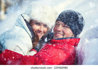Young happy embracing smiling couple winter outdoors portrait with falling snow. Bright white colors.