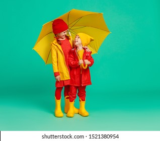 young happy emotional cheerful children friends laughing  with yellow umbrella   on colored green background