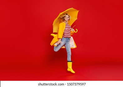 young happy emotional cheerful girl laughing  with yellow umbrella   on colored red background