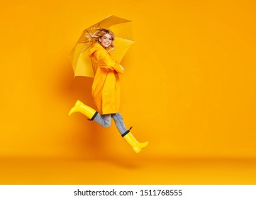 young happy emotional cheerful girl laughing  with umbrella   on colored yellow background