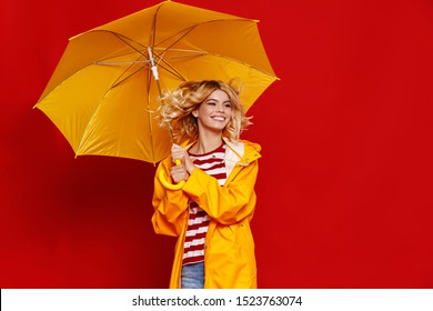 young happy emotional cheerful girl laughing and jumping with yellow umbrella   on colored red background