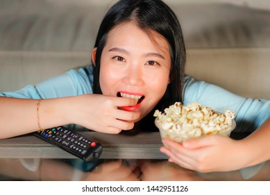 young happy and excited Asian Chinese woman with TV remote controller eating popcorn bowl watching television enjoying Korean drama or comedy movie having fun relaxed and cheerful