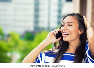 Young happy excited laughing woman talking on mobile phone isolated outdoors city urban background.