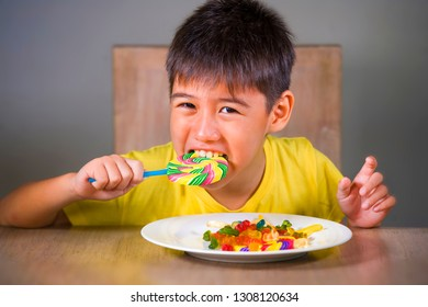 young happy and excited male kid smiling cheerful eating dish full of candy and lollipop sitting at table isolated on grey background in sugar addiction and abuse and sweet unhealthy nutrition