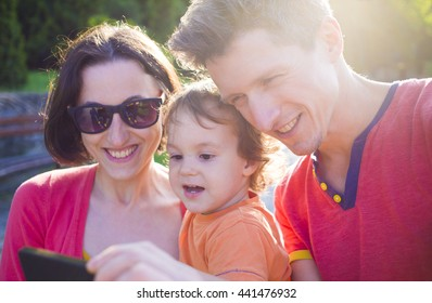 Young and happy family with a baby taking a selfie.