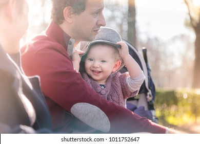 Young happy family with cheerful child having fun in park on sunny day.