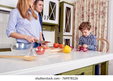 A young happy family is cooking at the big classic kitchen.