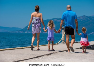 young happy family with cute little daughters holding their hands while walking by the sea during Summer vacation  Healthy family holiday concept