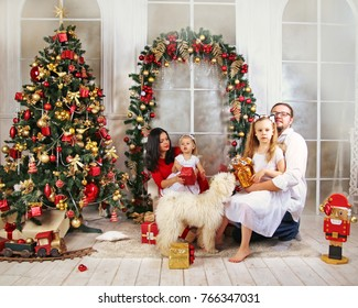 Young happy family with dog Puli on Christmas Eve. Father, mother and two little sisters into a decorated living room with new year tree