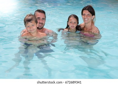 Young Happy family enjoying bath time in infinity pool