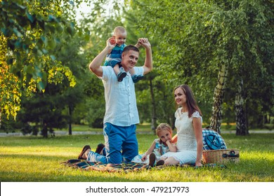Young happy family of four on picnic in the park