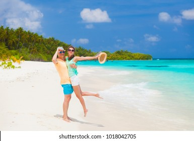 young happy family having fun on tropical beach.