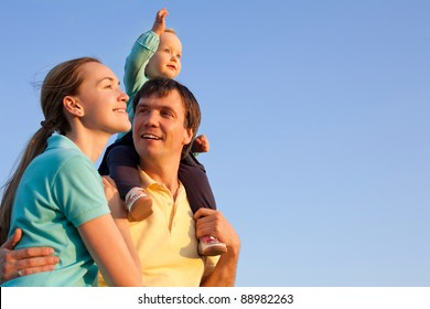 young happy family having fun outdoors with blue sky in background