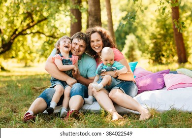Young happy family with kids having picnic with colored pillows outdoors. Parents with two children relax in a sunny summer garden. Mother, father, little girl and baby boy playing in park.