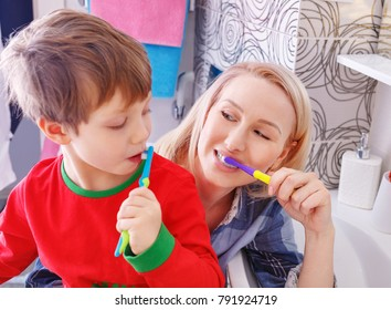 Young happy family. Mother and child little boy cleans teeth with a toothbrush in the bathroom. Healthy Mom and baby