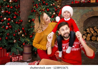 Young happy family: mother female woman, father male man and child kid boy in red santa hats and warm sweaters and celebrating Christmas Eve near decorated Christmas tree. Merry Christmas and New Year