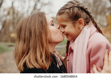 Young happy family in the park. Mother kissing daughter.