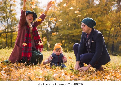The young happy family playing with leafs in the park