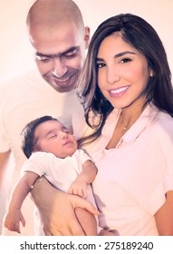 Young happy family portrait, cute adorable newborn daughter sleeping on mothers hands, father looking on his nice peaceful child, enjoying parenthood