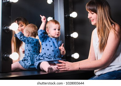 young happy family , shooting in the Studio. little girl with father and mother. in front of the mirror , sees the reflection