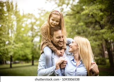 Young happy family spending time at park. Father carrying child on shoulders.