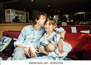 Young happy family spending time together in cafeteria or restaurant - husband kissing his wife while she is breast feeding their newborn little son. Parenthood and happy family concept.