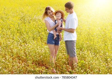 Young happy family with their infant boy at field