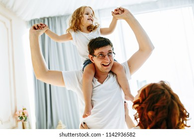 Young happy family of three having fun together in studio. Pretty little daughter on her father back. Father carrying daughter piggyback and being truly happy