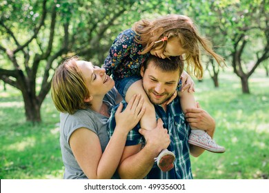 Young happy family of three playing in the park. Little girl having fun with her mother and father