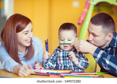 Young happy family with toddler boy playing together and having fun at home