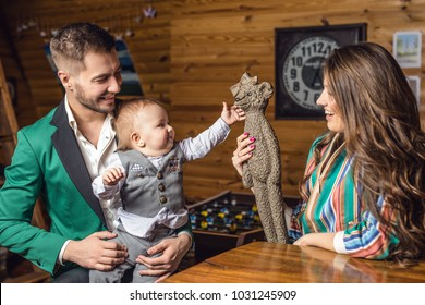Young happy family together in interior of wooden house.